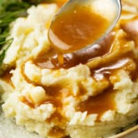 A spoon drizzling brown gravy over warm mashed potatoes.