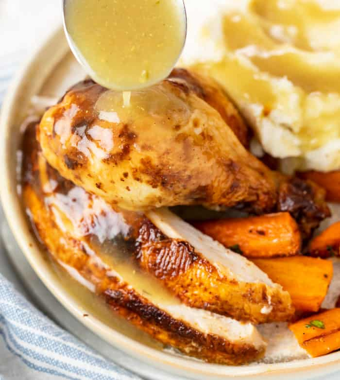 Roast Chicken being drizzled with homemade Chicken Gravy.