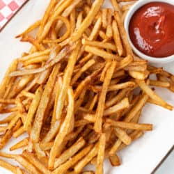 A white platter full of crispy homemade french fries next to a ramekin of ketchup.