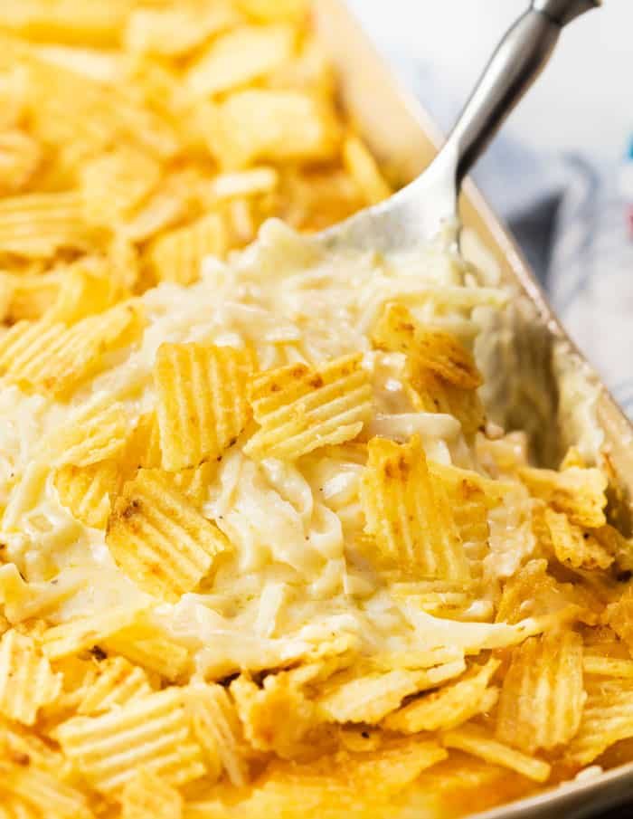 A spoon pulling up a scoop of creamy white funeral potatoes with potato chips on top.