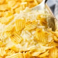 A spoon scooping up creamy funeral potatoes with crushed potato chips on top.