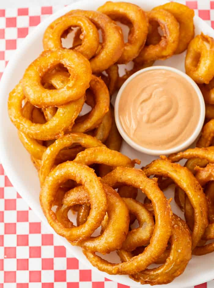 A white platter filled with deep fried onion rings with dipping sauce in the middle.