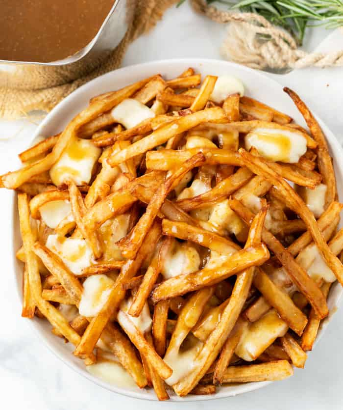 A white plate full of homemade poutine with french fries, gravy, and melted cheese curds.
