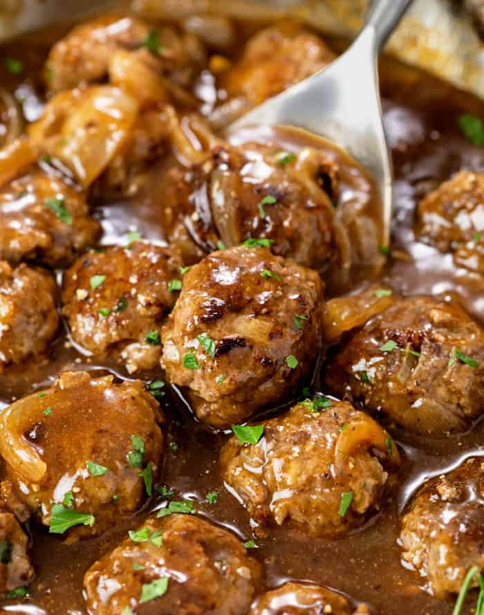 A skillet with meatballs and gravy topped with fresh parsley.