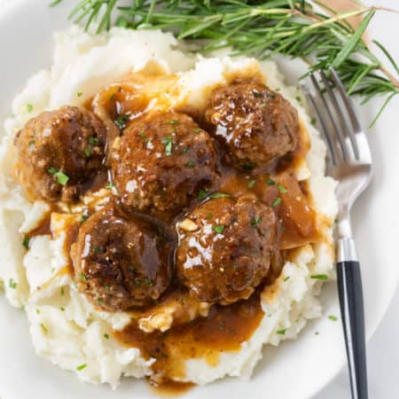 A white plate with a pile of mashed potatoes topped with meatballs and gravy with fresh rosemary on the side.
