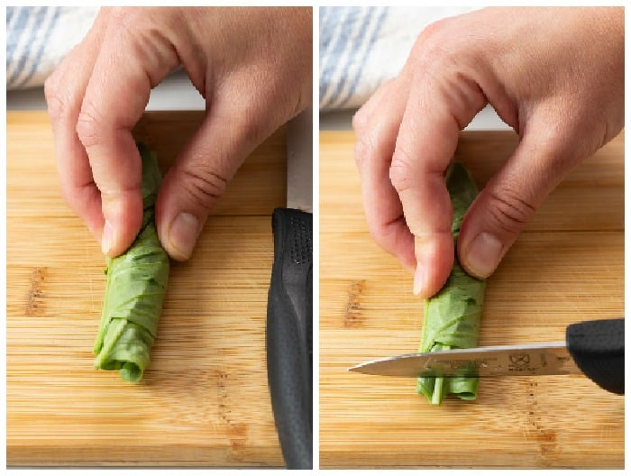A pairing knife slicing into rolled up basil.