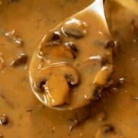 A spoon full of creamy mushroom gravy from a skillet.