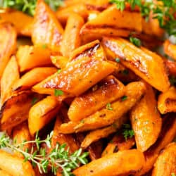 Sliced up roasted carrots piled on top of each other with fresh thyme on the side and in the back.