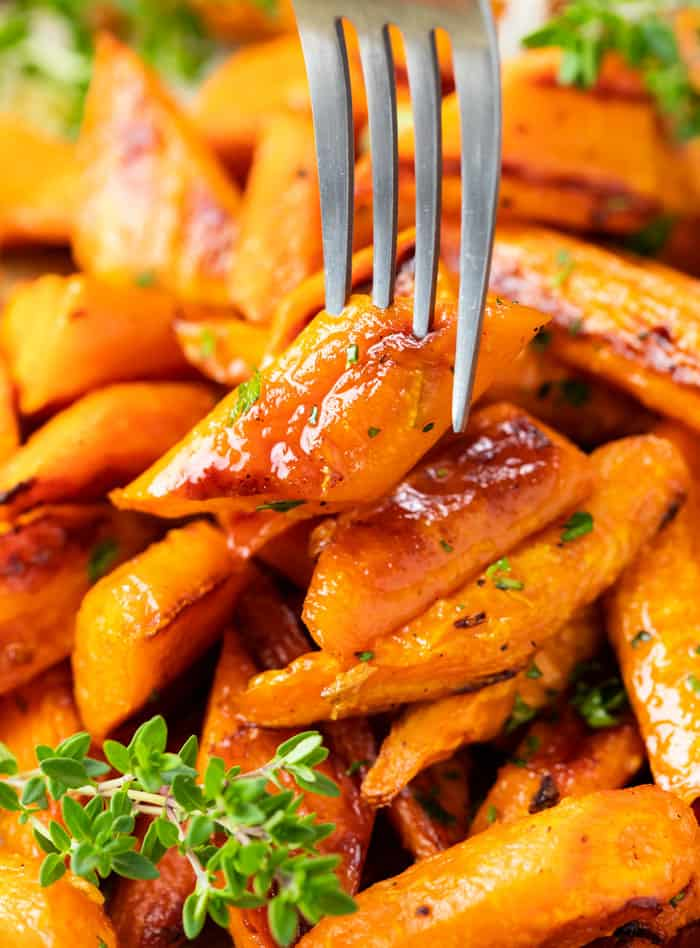 A fork picking up a roasted carrot from a pile.