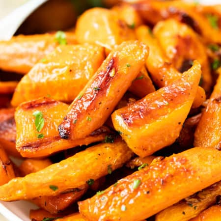 Roasted carrots in a white bowl with a spoon in the background.