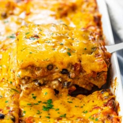 A casserole dish filled with Taco Lasagna that's being pulled up with a spatula.