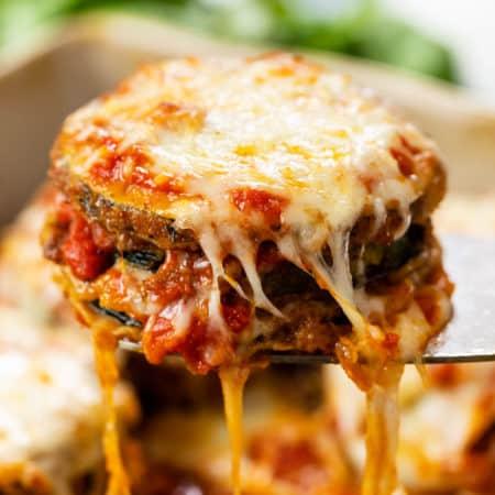 A spatula pulling up cheese zucchini parmesan from a casserole dish.