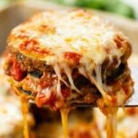 A cheesy stack of crispy breaded Zucchini Parmesan on a spatula.