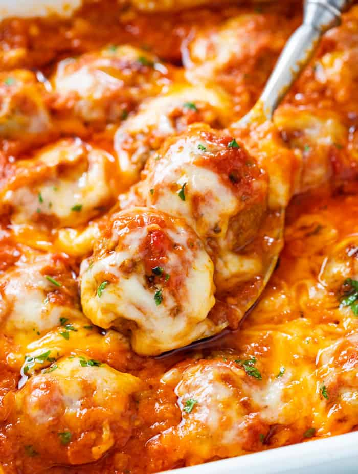 A spoon in a casserole dish full of baked meatballs in marinara sauce with melted cheese.