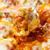 A spoon scooping up a meatball covered in marinara sauce and topped with cheese.