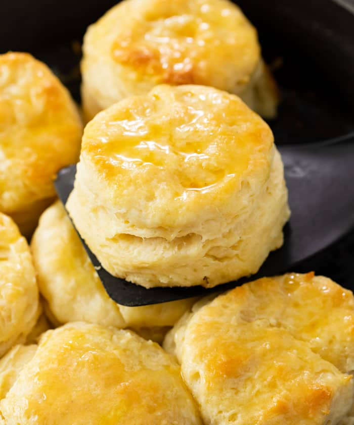 A buttermilk biscuit on a black spatula being pulled from a skillet.