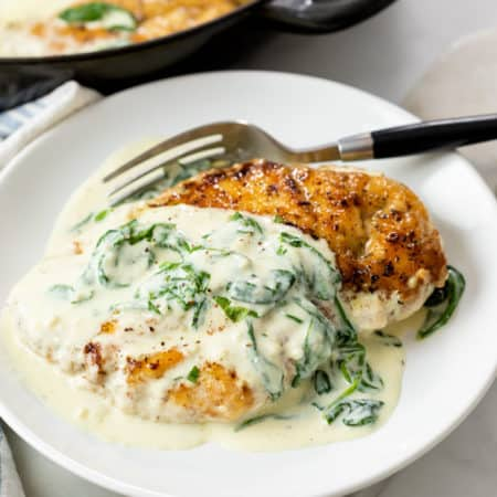 Chicken Florentine on a white plate with sauce on top and a fork in the back.