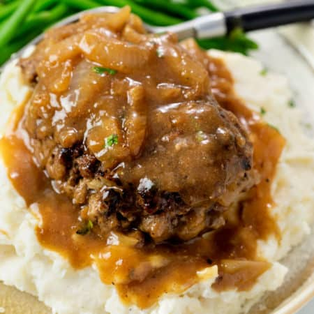 Hamburger Steak with Brown Gravy and Onions on a pile of mashed potatoes.