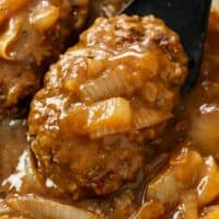 A spatula holding Hamburger Steak smothered in brown gravy with onions.