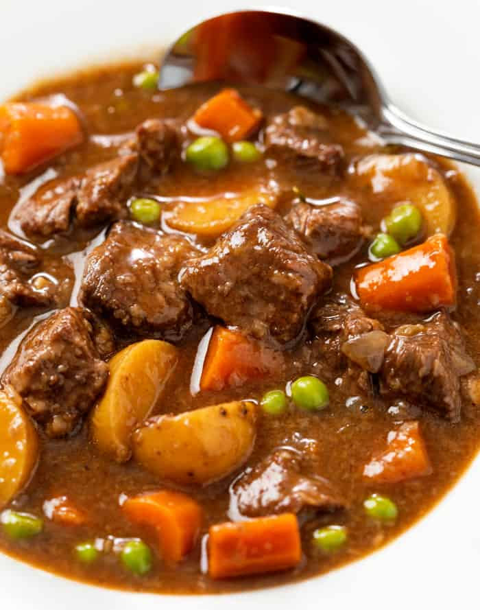 A white bowl filled with Slow Cooker Beef Stew with a spoon in the background.