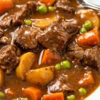 A close up view of Slow Cooker Beef Stew with beef, potatoes, carrots, peas, and red wine.