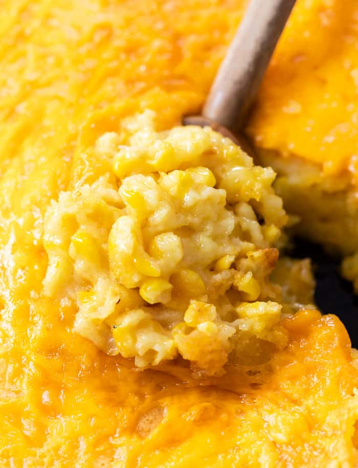 A wooden spoon scooping up Corn Casserole from a skillet.