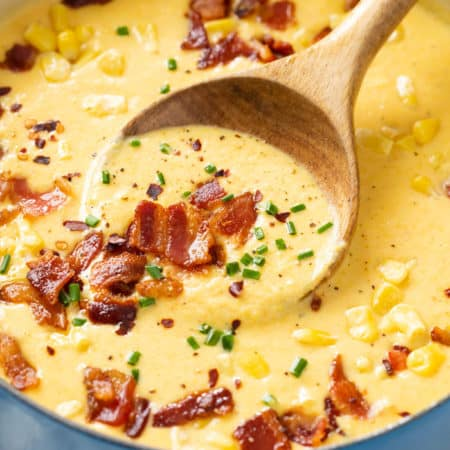 A soup pot filled with homemade Corn Chowder topped with bacon, chives, corn, and red pepper flakes.