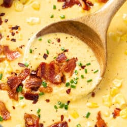 A wooden spoon filled with creamy corn chowder topped with bacon, chives and red pepper flakes.