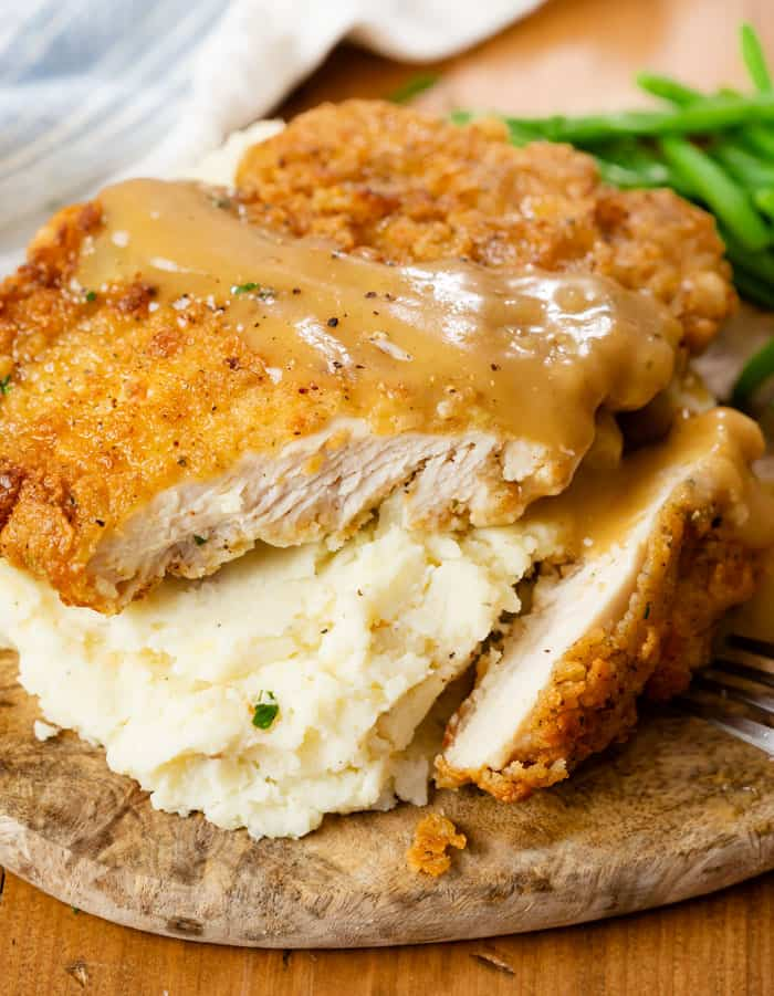 Country Fried Chicken over mashed potatoes with a slice cut into it and gravy on top.