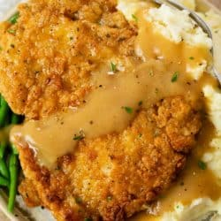Crispy Country Fried Chicken Topped with gravy over a pile of mashed potatoes.