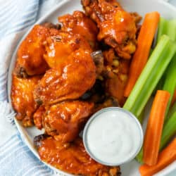 A plate with Buffalo Chicken Wings with a cup of blue cheese with celery and carrot sticks.