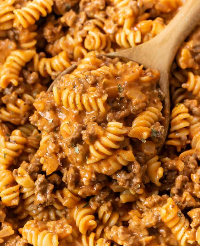 A wooden spoon full of creamy Ground Beef Pasta with Rotini noodles.