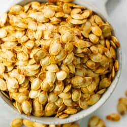 A white bowl overflowing with crispy roasted pumpkin seeds.
