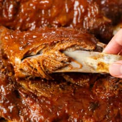 A hand pulling the bone out of tender Slow Coker ribs covered in BBQ Sauce