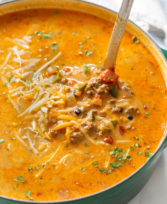 A soup pot filled with Taco Soup topped with melted cheese with a ladle scooping it up.