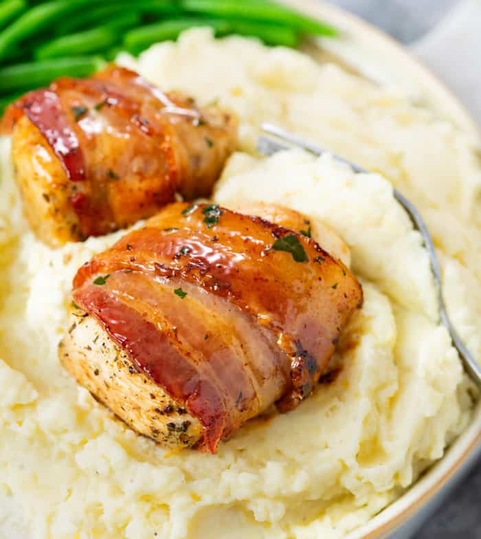 Bacon Wrapped Chicken on a pile of creamy mashed potatoes with green beans in the background.
