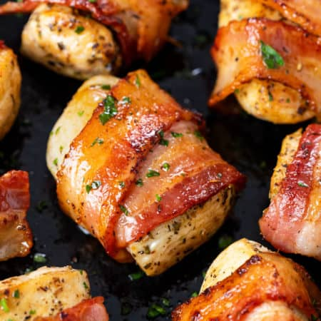 Seasoned chicken wrapped with crispy bacon in a skillet with parsley.