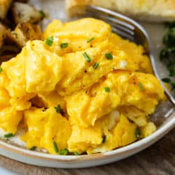 A plate with fluffy scrambled eggs topped with pepper and chives.