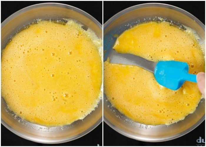 Whisked eggs in a pan with a spatula to make fluffy scrambled eggs.