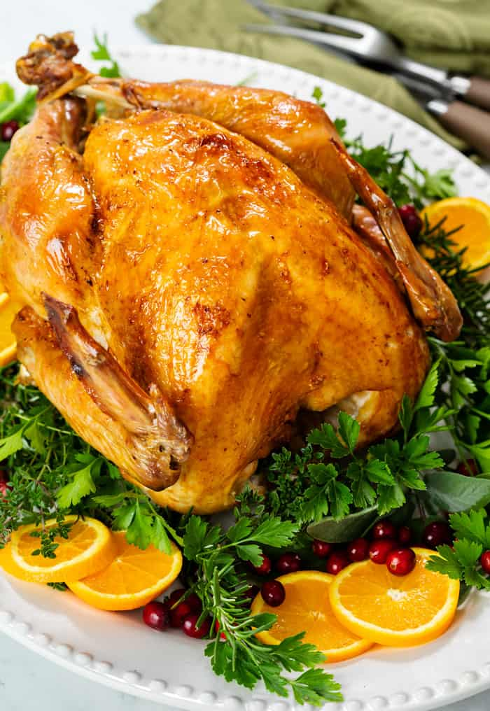 A roast turkey on a white platter with green parsley, sliced oranges, and fresh cranberries.
