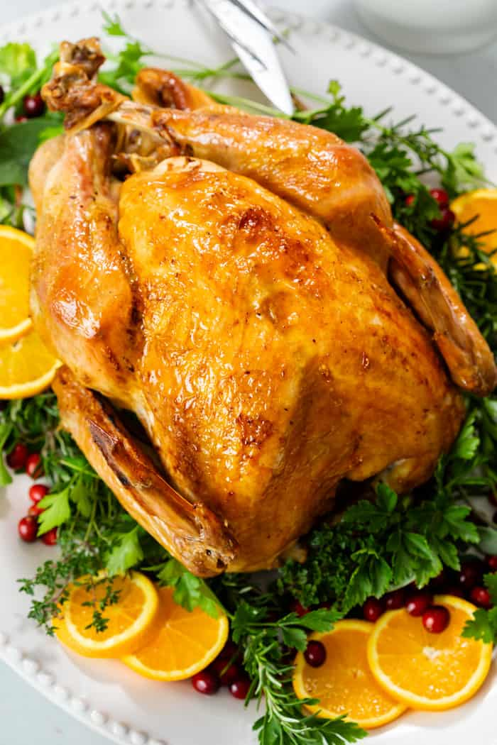 A golden roast turkey on a large serving platter with fresh herbs.