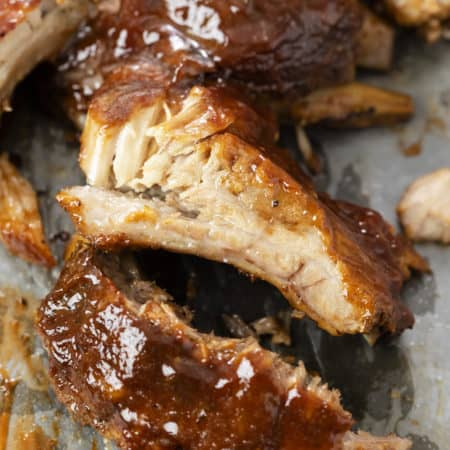 Slow Cooker Ribs topped with BBQ Sauce on parchment paper.