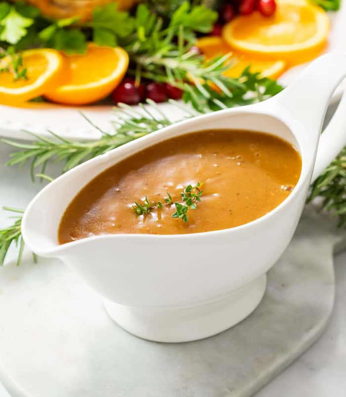Thick brown turkey gravy in a gravy boat topped with fresh thyme.
