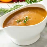 A white gravy boat filled with thick turkey gravy topped with fresh thyme.