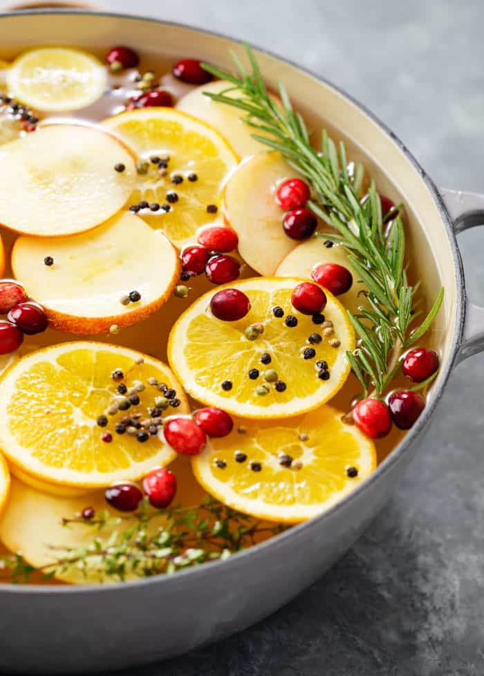 A bowl full of wet brine for a turkey with sliced fruit, fresh cranberries, and rosemary.