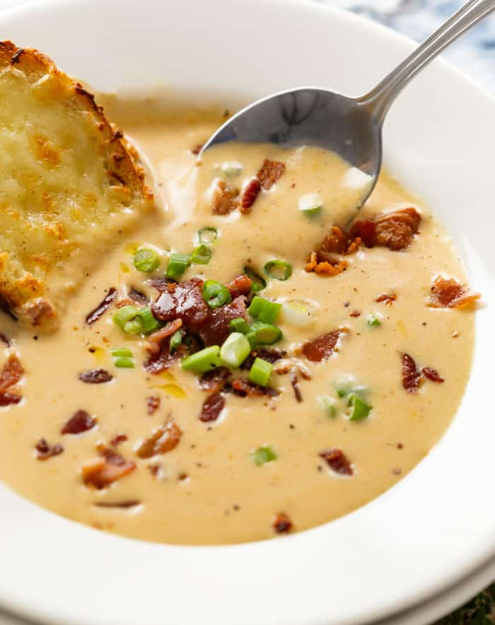 A white bowl full of beer cheese soup topped with green onions and bacon with a spoon in the background.