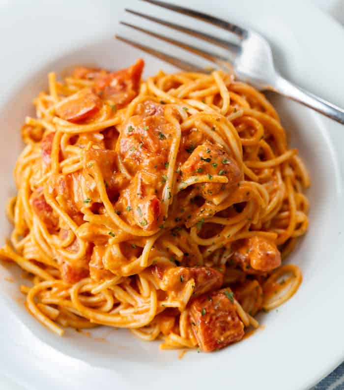 A white plate filled with creamy tomato pasta with a fork on the side.