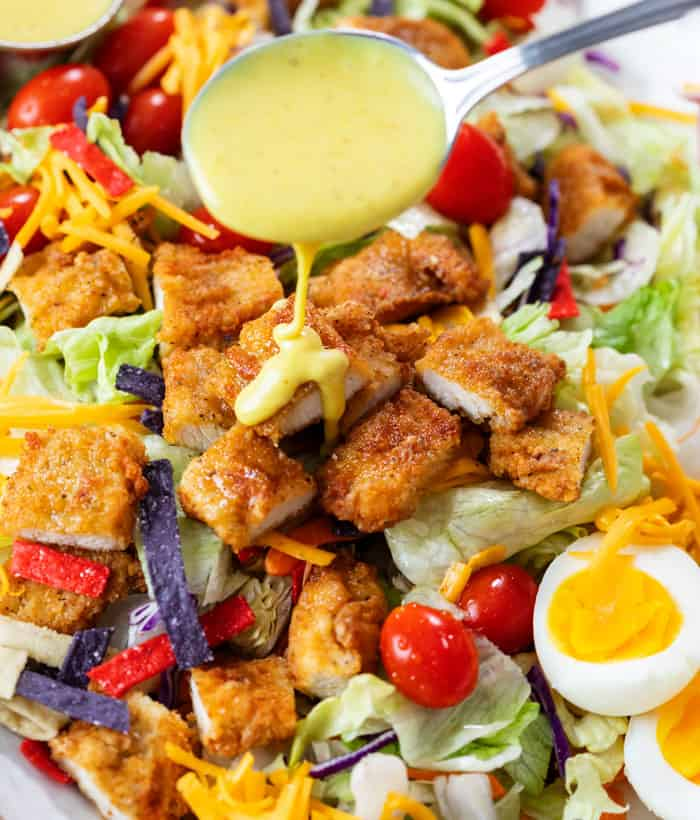 A spoon drizzling honey mustard over a crispy chicken salad.