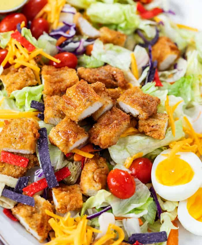 Crispy Chicken Salad with breaded chicken strips, lettuce, tomatoes, hard boiled eggs, cheese, and crispy tortilla crisps.