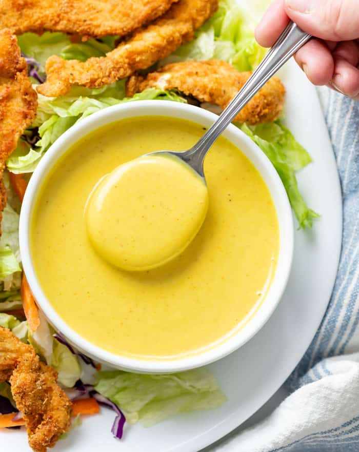 Overhead view of a white bowl of honey mustard with a spoon in it.